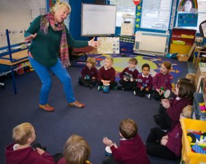 Lilian Ross is singing a song with actions to young pupils.