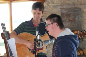 Student and teacher record a song they've written during the project